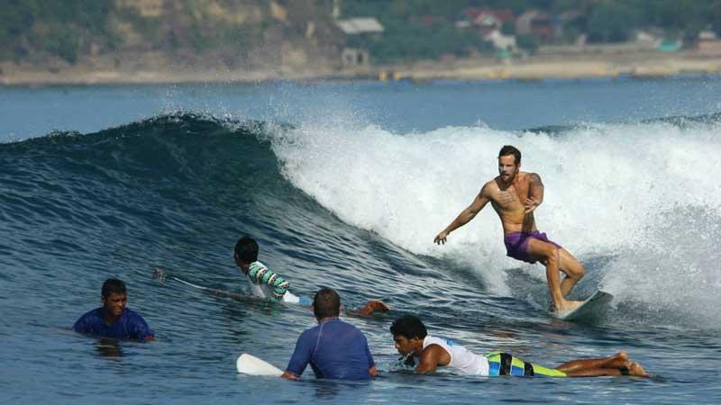 Jag surfar på ett rev utanför ön kuta Lombok, Indonesien