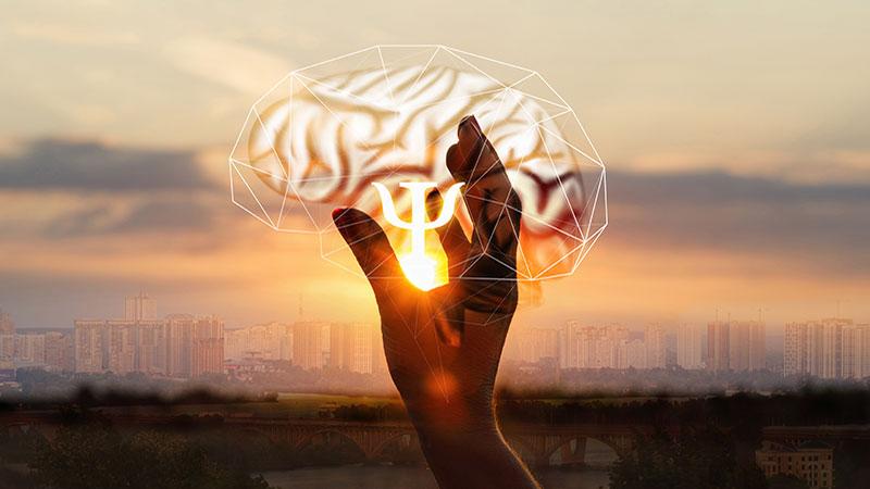 I handen syns den grekiska bokstaven Psi som symboliserar psykologi.